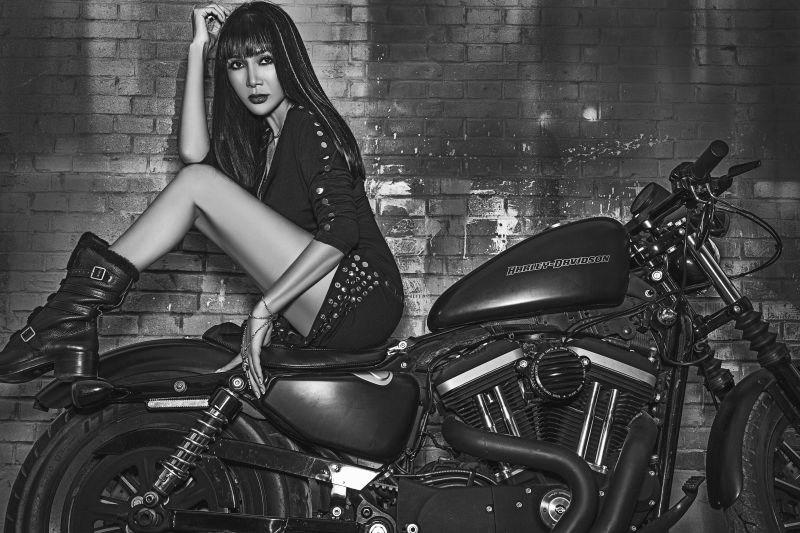 张咪身着黑色铆钉短裙,脚穿黑色长靴,跨坐在摩托车上,风情万种(图片)